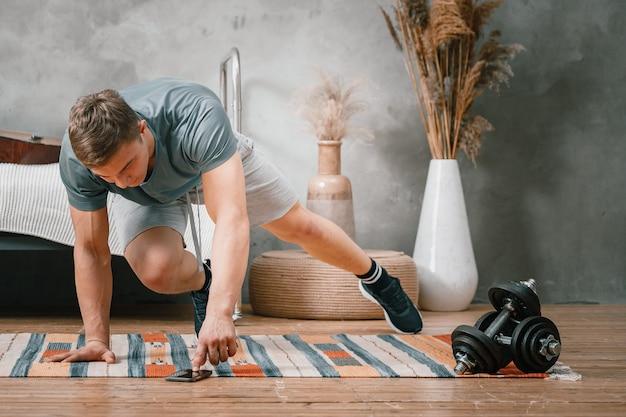 Młody człowiek uprawia sport w domu, trening online przez telefon. sportowiec rzuca się, ogląda film i portale społecznościowe w sypialni