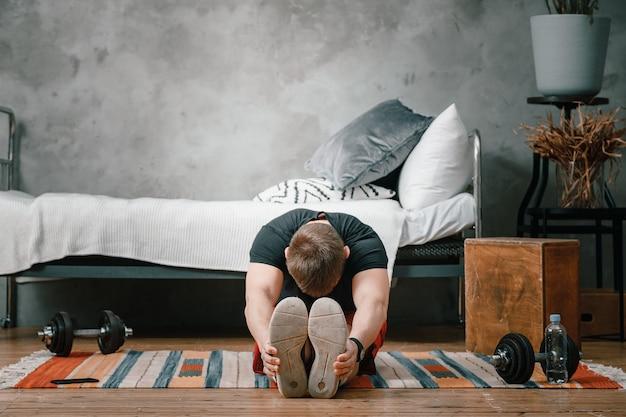 Młody człowiek uprawia sport w domu, trening online przez telefon. sportowiec wyciągający się w sypialni, w tle łóżko, wazon, dywan.