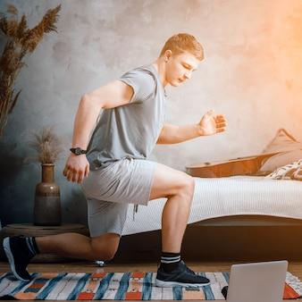 Młody człowiek uprawia sport w domu, trening online z laptopa. sportowiec rzuca się, ogląda film w sypialni, w tle łóżko, wazon, dywan.