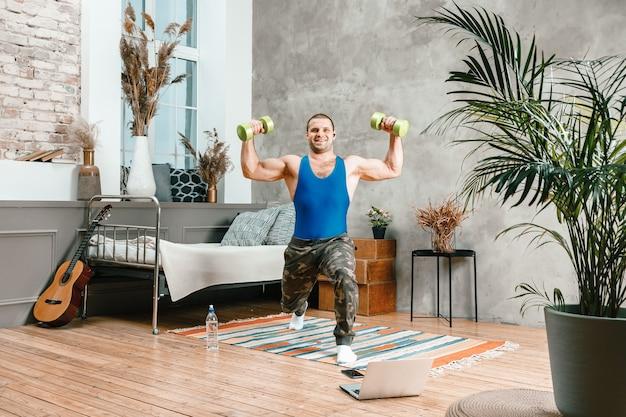 Młody człowiek uprawia sport w domu, trening online z laptopa