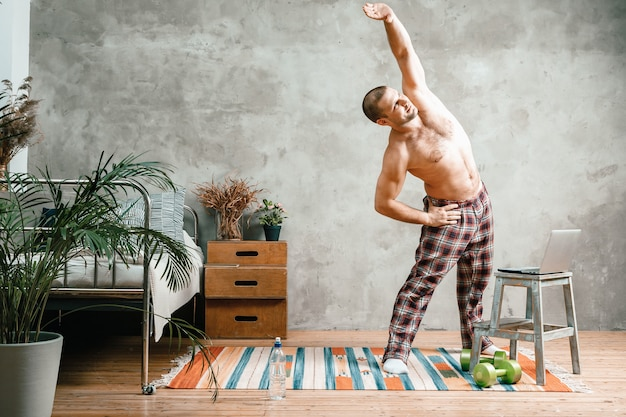 Młody człowiek uprawia sport w domu, trening online