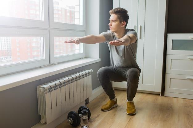 Młody człowiek uprawia sport w domu. zajęcia sportowe w domu