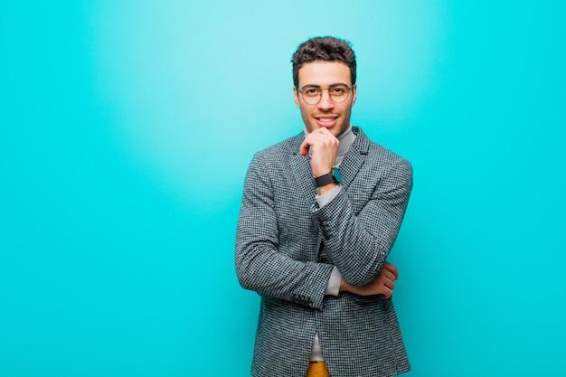 Młody człowiek uśmiecha się, ciesząc się życiem, czując się szczęśliwy, przyjazny, zadowolony i beztroski z ręką na brodzie na niebieską ścianą