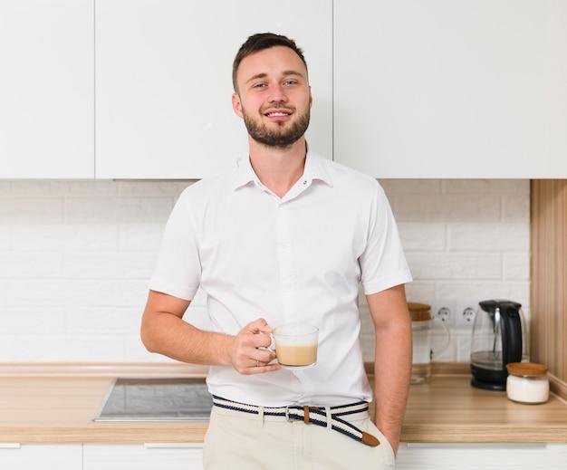 Młody człowiek uśmiecha się do kamery z kawą