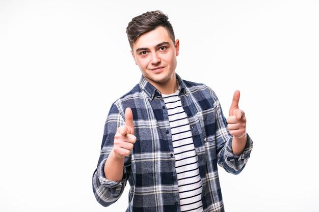 Młody człowiek uśmiecha się dobrego symbol przed biel ścianą i robi