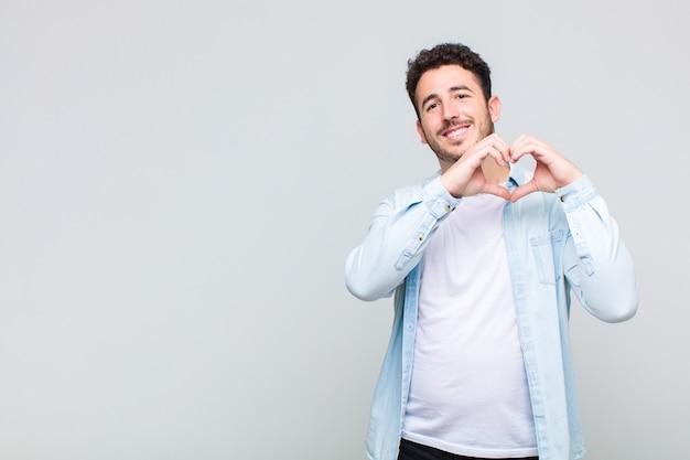 Młody człowiek uśmiecha się i czuje się szczęśliwy, uroczy, romantyczny i zakochany, tworząc kształt serca obiema rękami