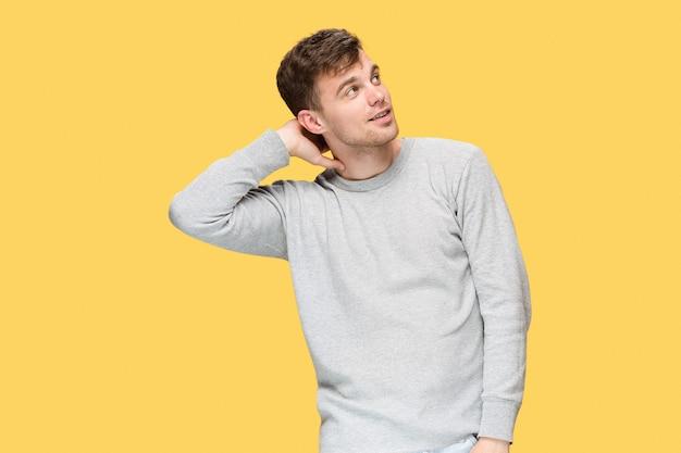 Młody człowiek uśmiecha się i odwraca wzrok na żółtym tle