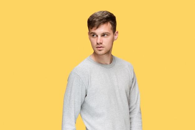 Młody człowiek uśmiecha się i patrząc na kamery na żółtym tle