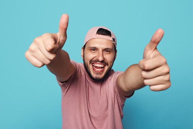 Młody człowiek uśmiecha się i pokazuje kciuk w górę na białym tle nad niebieską ścianą