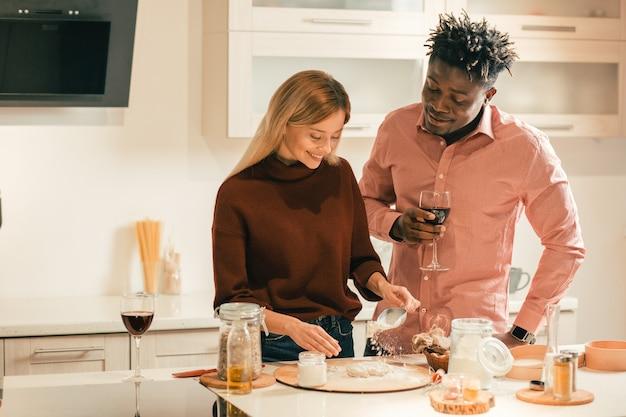 Młody człowiek uśmiecha się i trzyma kieliszek wina, podczas gdy jego wesoła dziewczyna robi ciasto