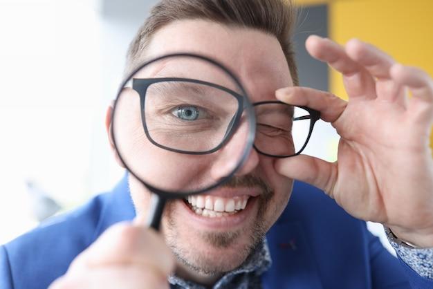Młody człowiek uśmiecha się i trzyma szkło powiększające przed jego zbliżenie oczu