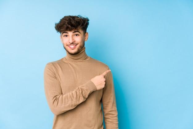 Młody człowiek uśmiecha się i wskazuje na bok, pokazując coś w pustej przestrzeni
