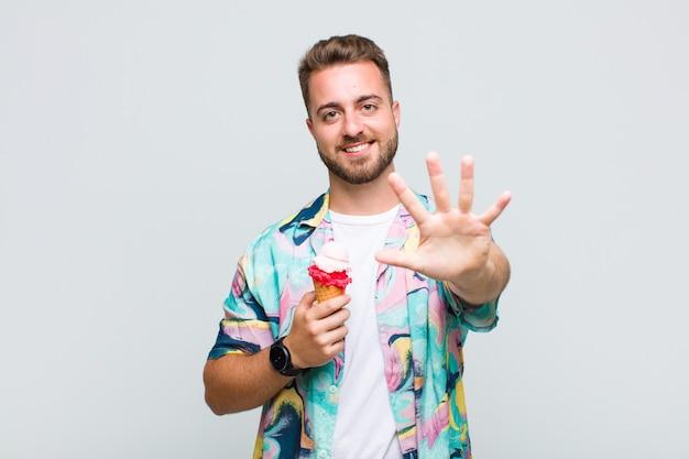 Młody człowiek uśmiecha się i wygląda przyjaźnie, pokazując numer pięć lub piąty z ręką do przodu, odliczając