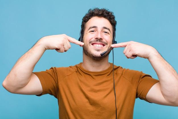 Młody człowiek uśmiecha się pewnie, wskazując na swój szeroki uśmiech, pozytywne, zrelaksowane, zadowolone nastawienie