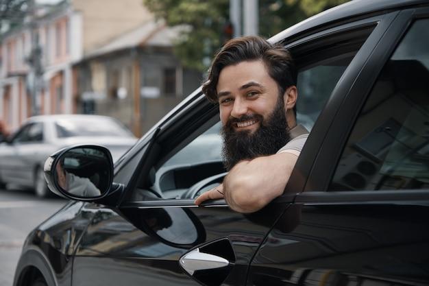 Młody człowiek uśmiecha się podczas jazdy samochodem