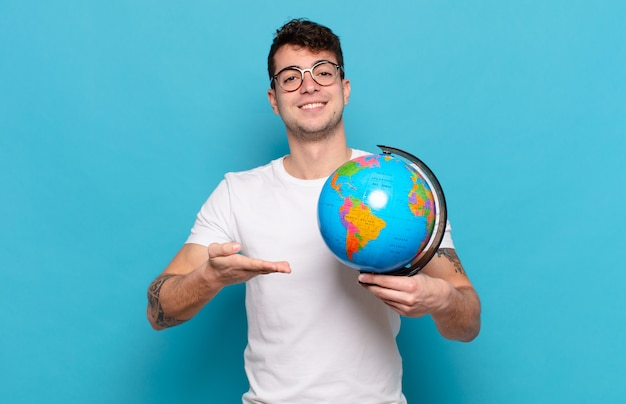 Młody człowiek uśmiecha się radośnie, czuje się szczęśliwy i pokazuje koncepcję w przestrzeni kopii z dłoni