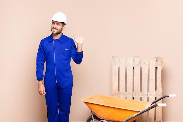 Młody człowiek uśmiecha się radośnie i wesoło, macha ręką, wita i wita lub żegna się z koncepcją budowy