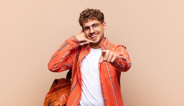 Młody człowiek uśmiecha się radośnie i wskazuje na aparat podczas rozmowy na białym tle