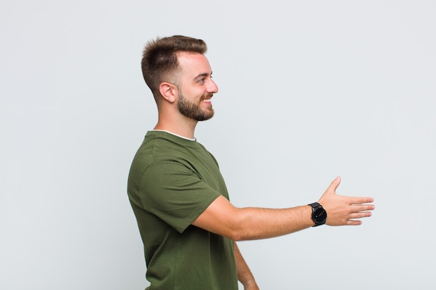 Młody człowiek uśmiecha się, wita i oferuje uścisk dłoni, aby zamknąć udaną transakcję, koncepcja współpracy