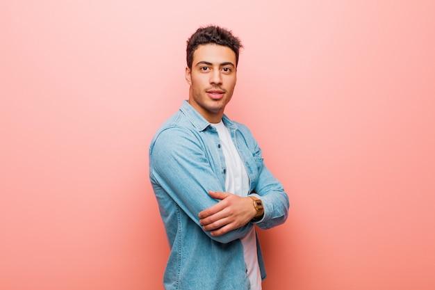 Młody człowiek uśmiecha się ze skrzyżowanymi rękami i szczęśliwy, pewny siebie, zadowolony wyraz twarzy z boku na różowej ścianie