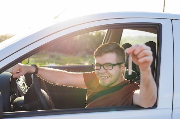 Młody człowiek uśmiechając się i trzymając klucz w swoim samochodzie. koncepcja zakupu samochodów i ludzi