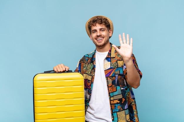 Młody człowiek uśmiechający się radośnie i radośnie, machający ręką, witający cię i witający lub żegnający. koncepcja wakacje