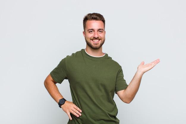 Młody człowiek uśmiechnięty, czujący się pewnie, odnoszący sukcesy i szczęśliwy, pokazujący koncepcję lub pomysł na kopii przestrzeni z boku