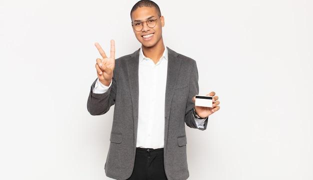 Młody człowiek uśmiechnięty i wyglądający przyjaźnie, pokazujący numer dwa lub sekundę z ręką do przodu, odliczający
