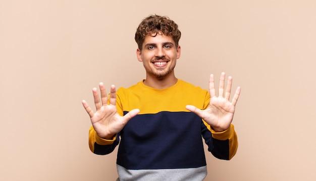 Młody człowiek uśmiechnięty i wyglądający przyjaźnie, pokazujący numer dziesięć lub dziesiątą z ręką do przodu, odliczający