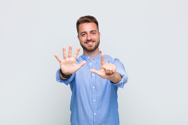 Młody człowiek uśmiechnięty i wyglądający przyjaźnie, pokazujący numer siedem lub siódmy z ręką do przodu, odliczający
