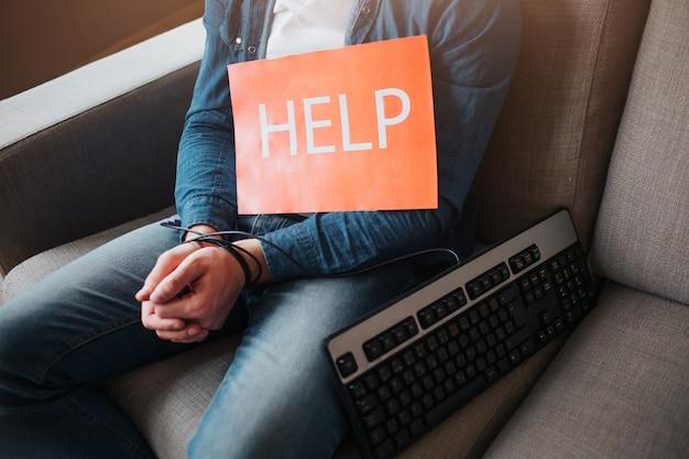 Młody człowiek uzależniony jest od mediów społecznościowych. uzależnienie od laptopa lub smartfona. ręce są owinięte. laptop poza tym na kanapie. pomoc papieru.