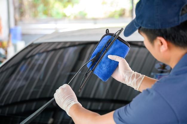 Młody człowiek użył niebieskiego ręcznika, aby wytrzeć wycieraczki samochodowe i pióra wycieraczek, aby wyczyścić gumę wycieraczek samochodowych.