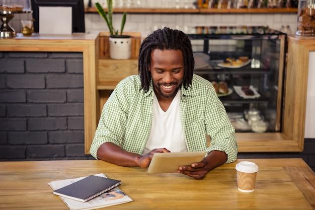 Młody człowiek używa cyfrową pastylkę w bufecie