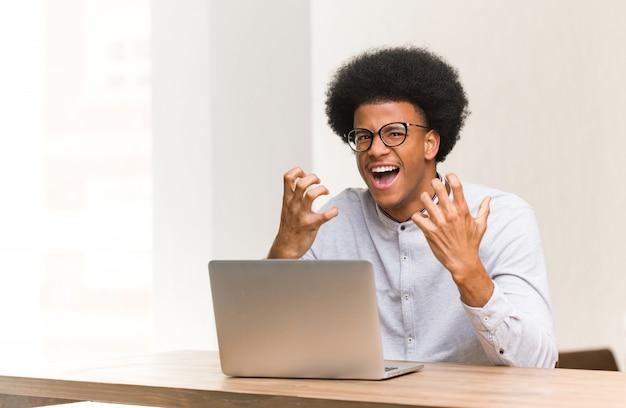 Młody człowiek używa jego laptop gniewnego i wzburzonego