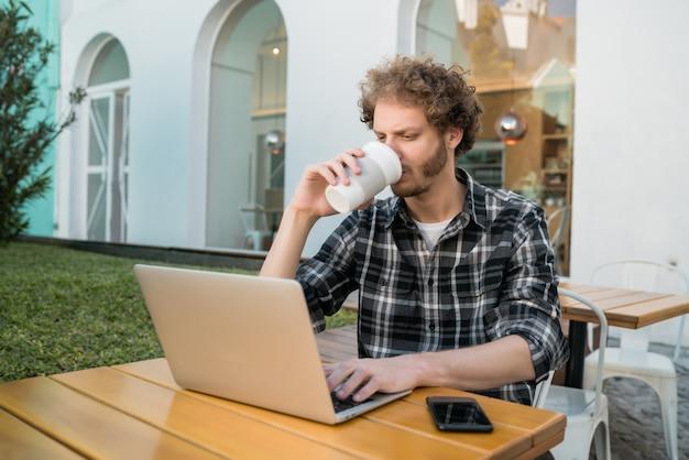 Młody człowiek używa jego laptop w sklep z kawą.