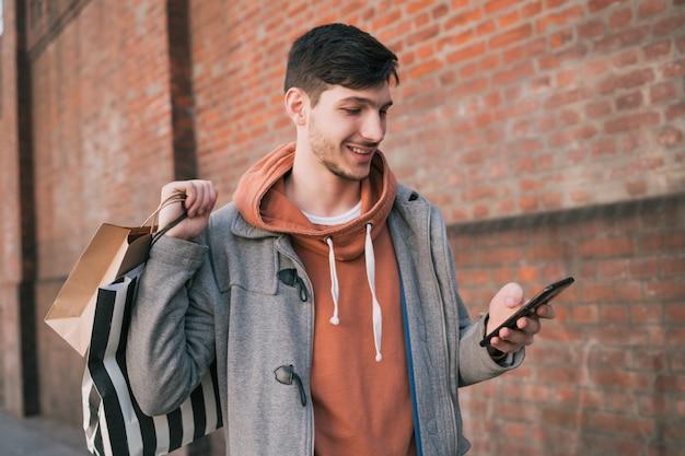 Młody człowiek używa jego telefon komórkowego na ulicie.