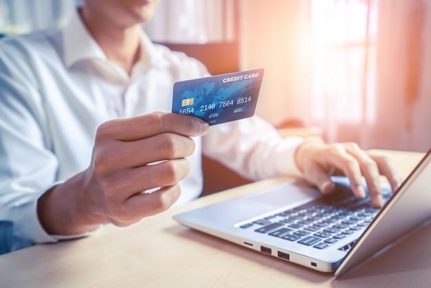 Młody człowiek używa karty kredytowej do płatności za zakupy online w aplikacji komputera przenośnego lub na stronie internetowej