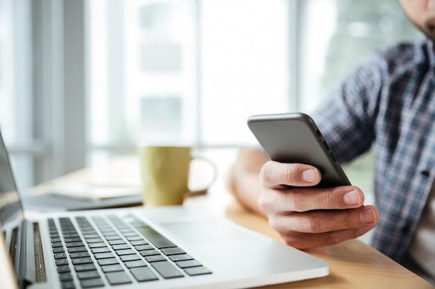 Młody człowiek używa laptop i telefon.