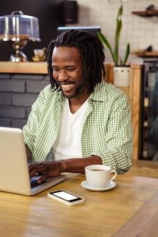 Młody człowiek używa laptop w bufecie