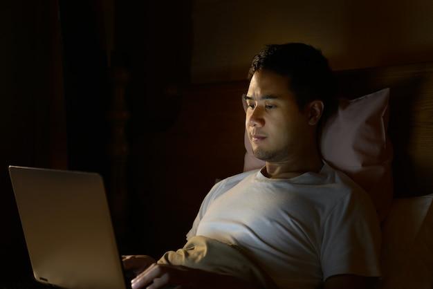 Młody człowiek używa laptop w jego łóżku przy nocą