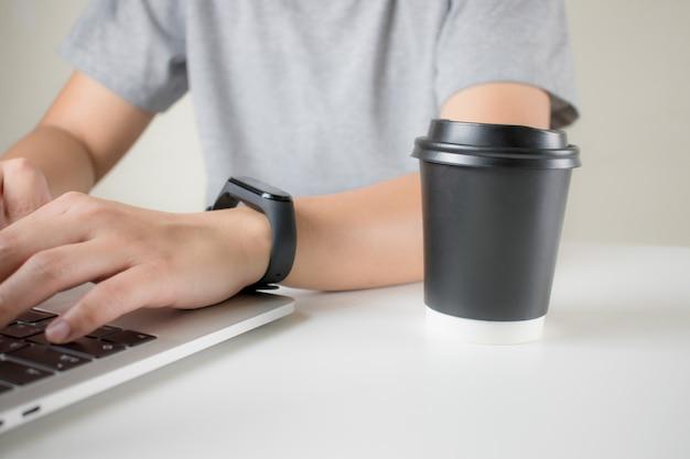 Młody człowiek używa laptop z kawą w biurze. widok z boku