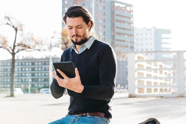 Młody człowiek używa mądrze telefonu obsiadanie na ławce przeciw miasto budynkowi