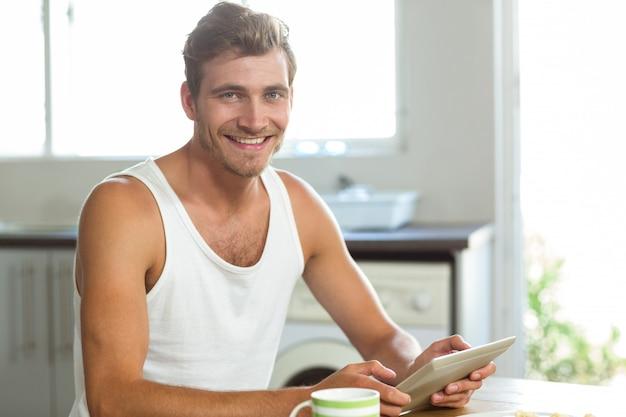 Młody człowiek używa pastylka peceta przy śniadaniowym stołem