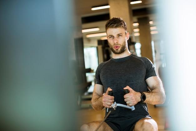 Młody człowiek używa posadzoną rząd maszynę w gym