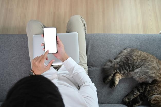 Młody człowiek używa smartfona i siedzi z kotem na kanapie