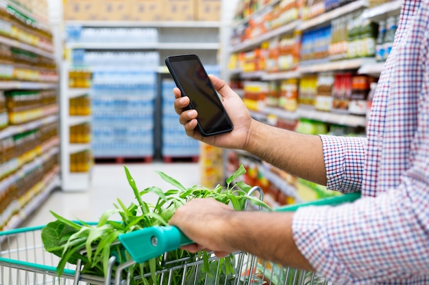 Młody człowiek używa smartphone podczas gdy robiący zakupy przy supermarketem.