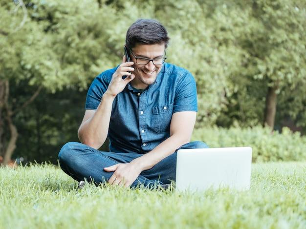 Młody człowiek używa smartphone podczas gdy siedzący na trawie