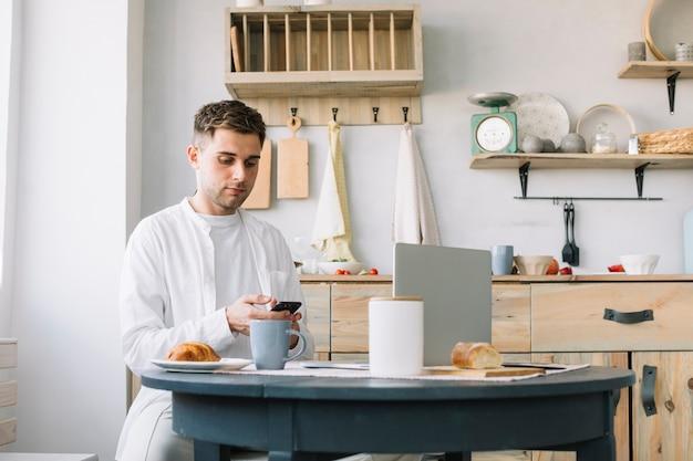 Młody człowiek używa smartphone siedzi blisko stołu z śniadaniem i laptopem w kuchni