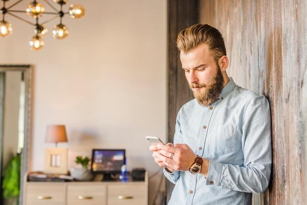 Młody człowiek używa smartphone w domu