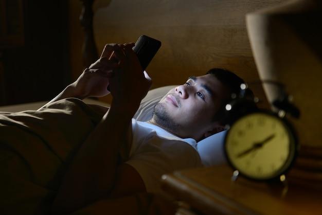 Młody człowiek używa smartphone w jego łóżku przy nocą